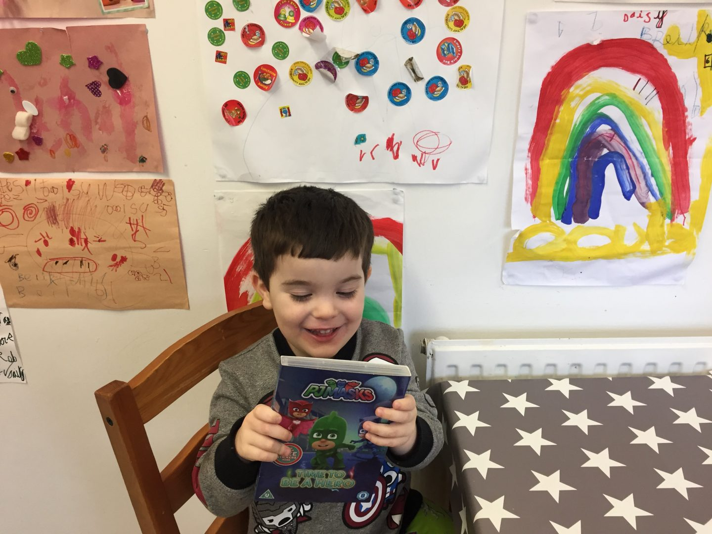 smiling boy holding pj masks time to be a hero dvd