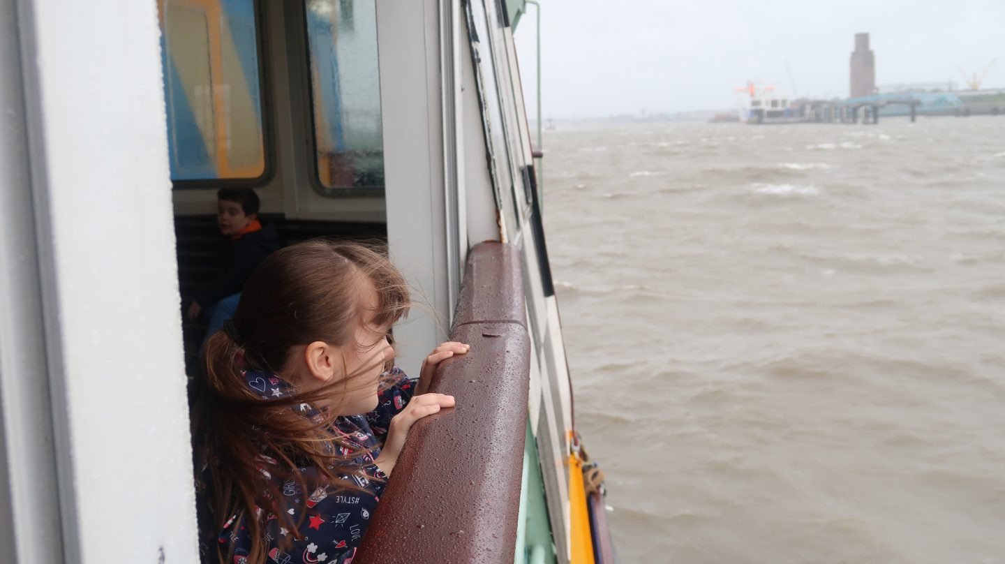 girl looking at liverpool waterfront from mersey ferry snowdrop