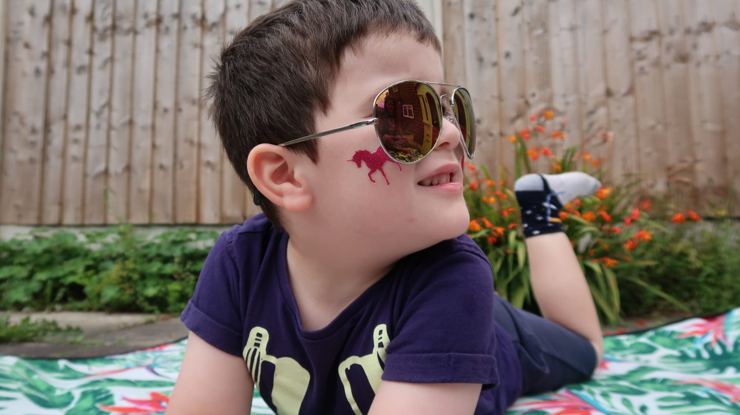 boy in sunglasses wearing fablab temporary face tattoo
