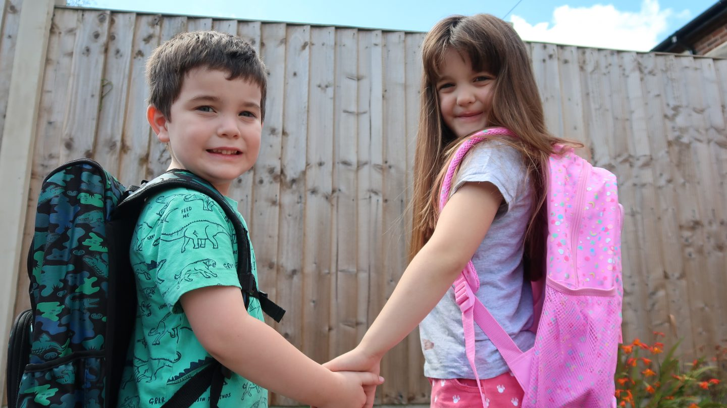 borther and sister holding hands wearing smiggle backpacks