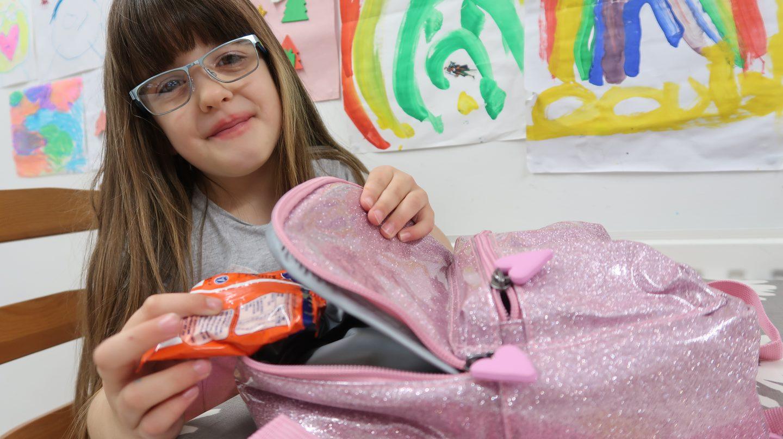 girl filling sparkly pink backpack
