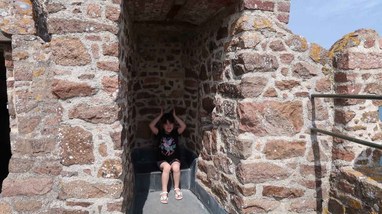 girl sitting at Mont Orgueil Castle Jersey