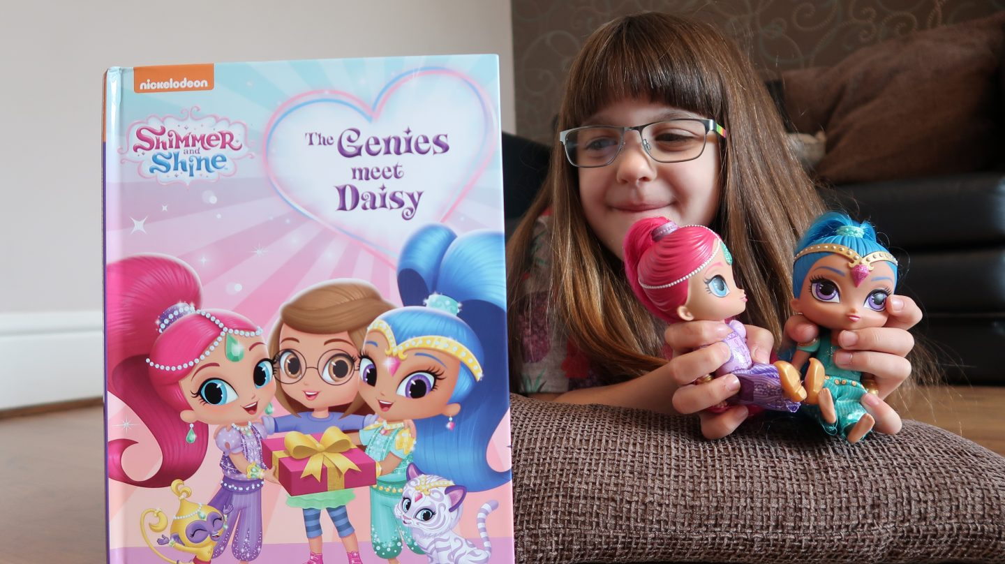 girl in glasses looking at penwizard shimmer and shine book holding dolls