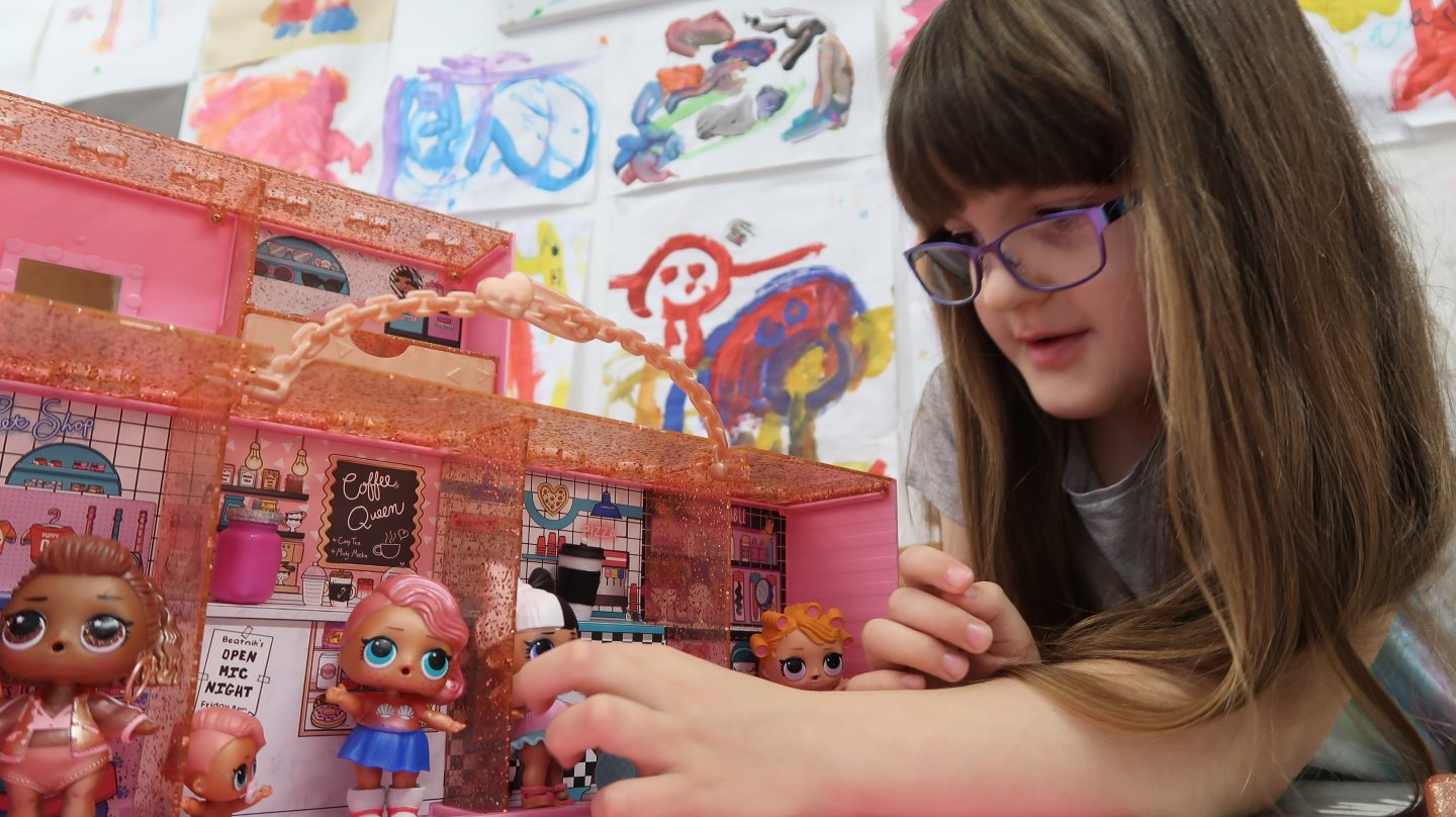 girl playing with lol doll pop up store surprise