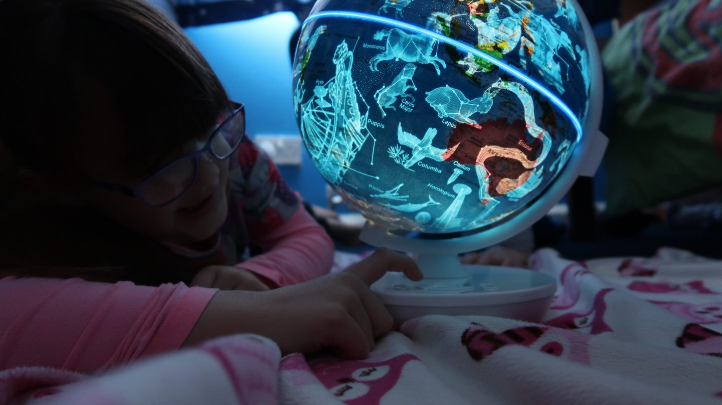 girl looking at smart globe myth illuminated constellations