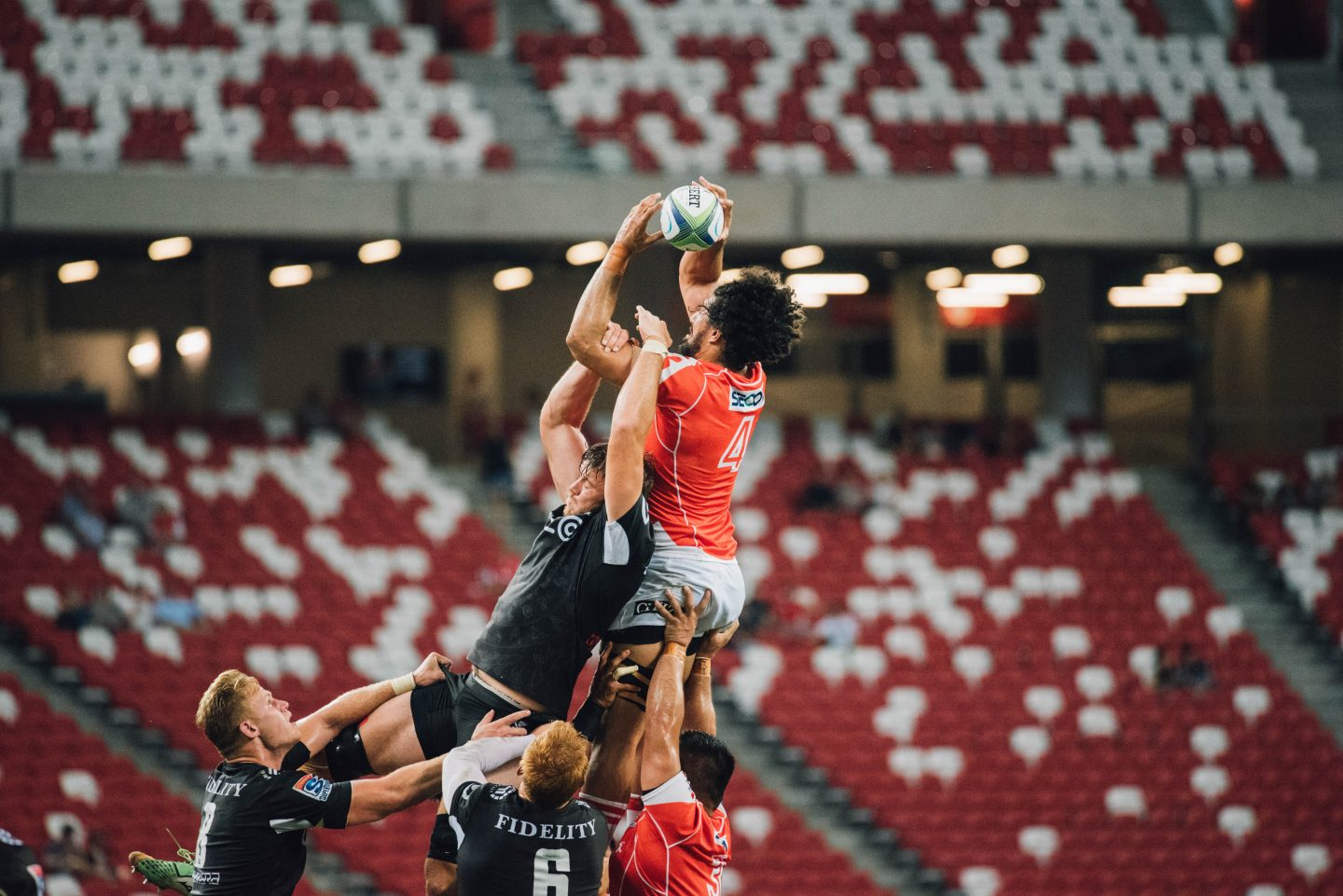 rugby players lifting team mate to catch line out