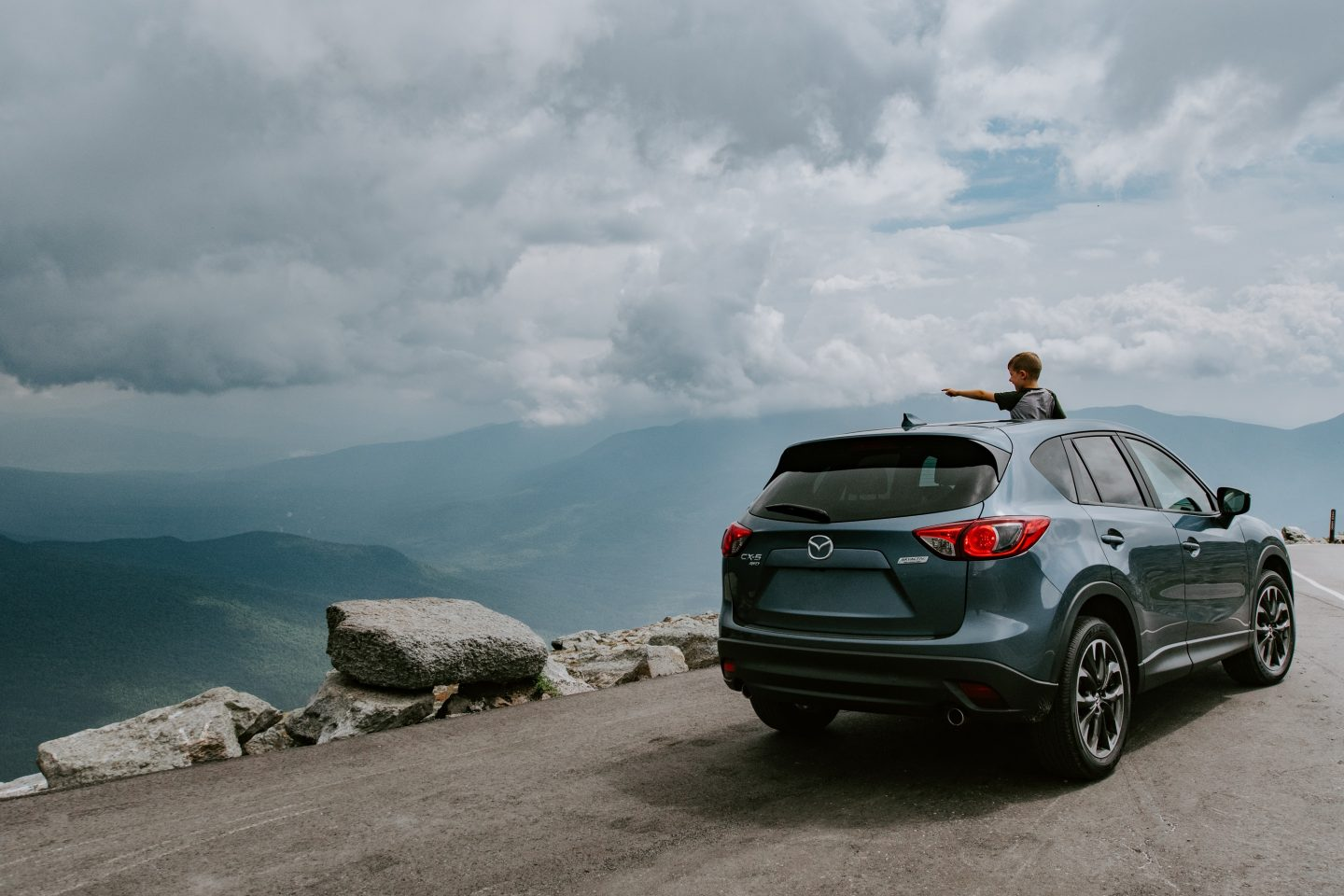 Child standing through the sunroof of a car on a mountain mountain pass